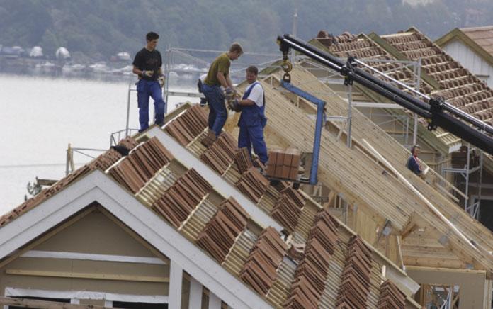Snekkere på taket på et nybygg